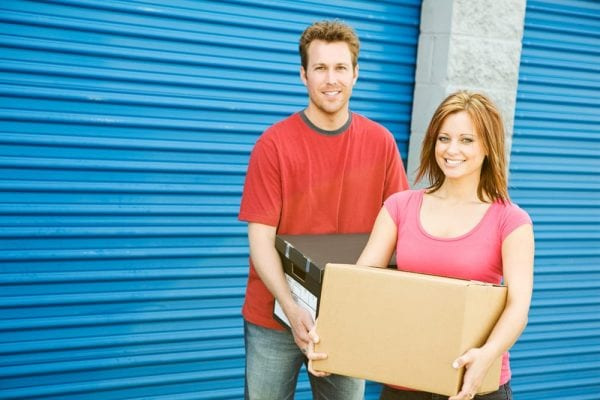 a man and a woman carrying boxes while standing in front of a blue storage unit