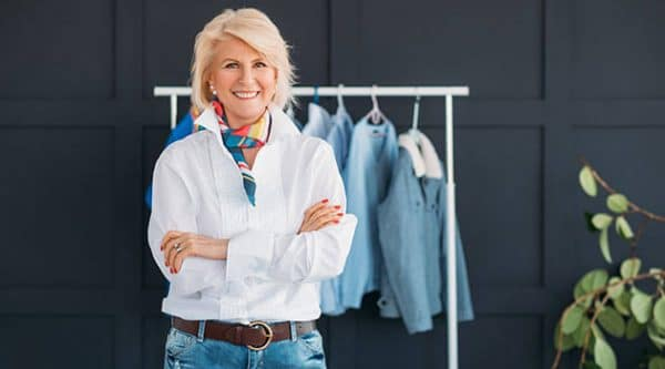 a fashionable middle aged woman standing in front of her wardrobe