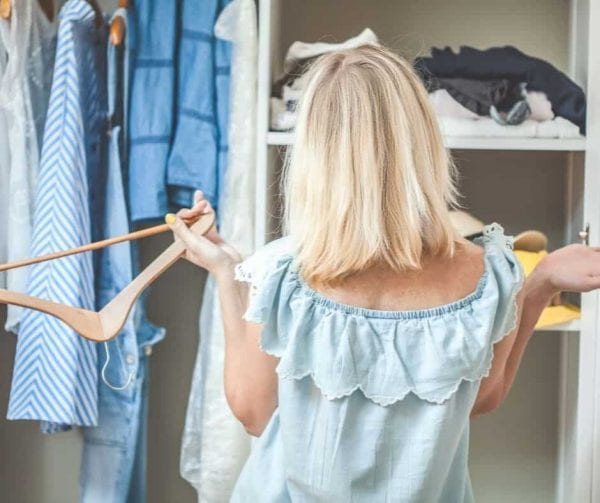 a woman in a blue dress holding a clothes hanger