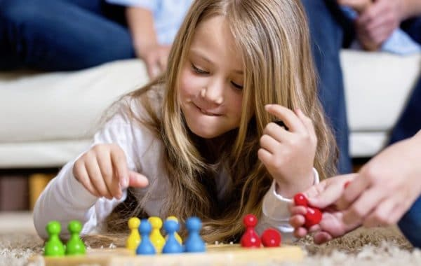 a girl playing chess on the living room floor