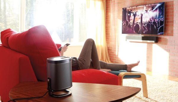 a man slouching on the couch while streaming a concert