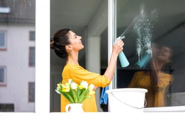 a woman in a yellow shirt cleaning her glass windows