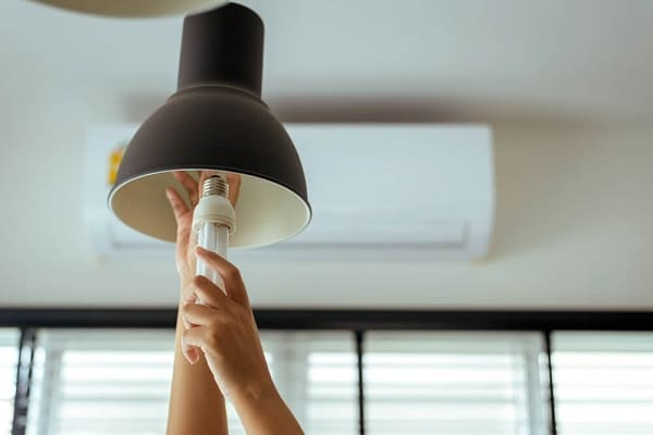 A person changing the light bulb