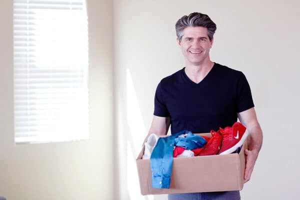 A man carrying a box with clothes